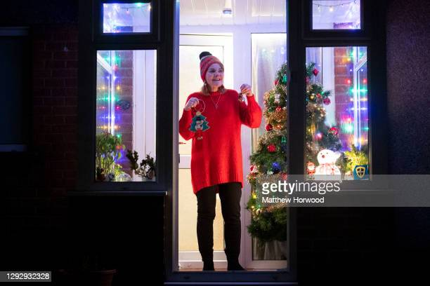 Woman rings bells from the doorstep of her house in Rhiwbina on December 24, 2020 in Cardiff, Wales. The event, sparked by Mary Beggs-Reid, from...