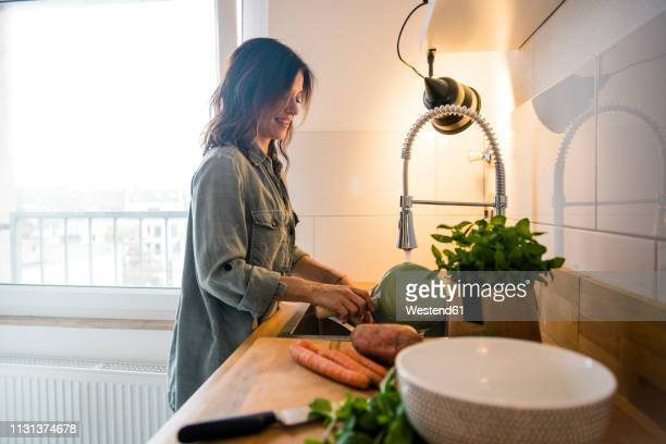 woman rinsing pot in the sink of her kitchen - washing up stock pictures, royalty-free photos & images