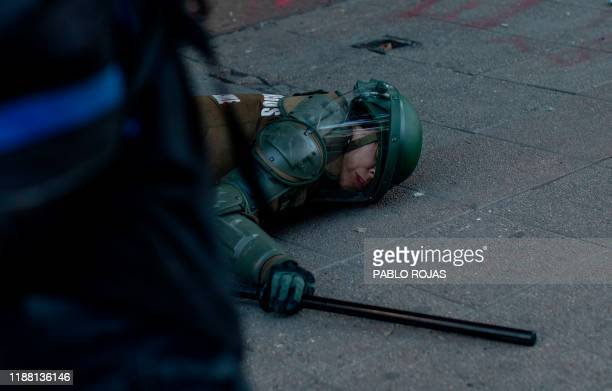 A woman riot police officer lays injured on the floor after being attacked by demonstrators during a protest against the government in Santiago on...