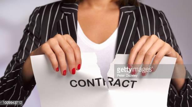 woman ripping up work contract - annullamento foto e immagini stock