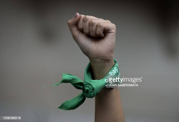 A woman rises her fist with a green headscarves to demand the legalization of abortion during a demonstration in front of the Congress during a women...