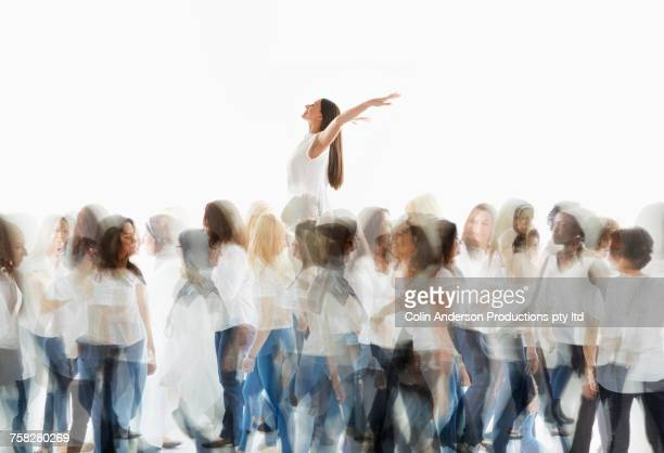 Woman rising above crowd and celebrating