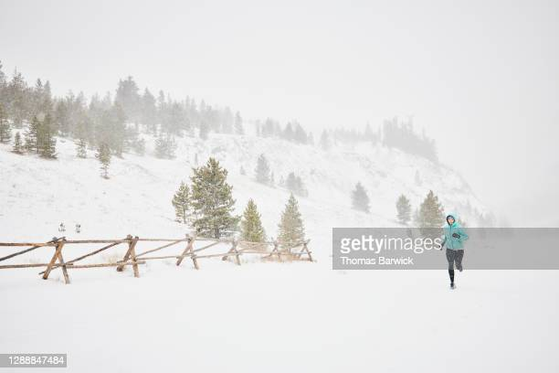 woman road running during blizzard - forward athlete stock pictures, royalty-free photos & images