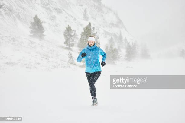 woman road running during winter snow storm - forward athlete stock pictures, royalty-free photos & images