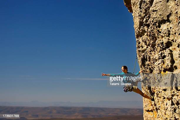 Woman rock climbing and pointing