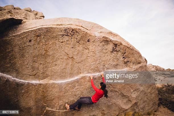 Woman rock climbing, Buttermilk Boulders, Bishop, California, USA