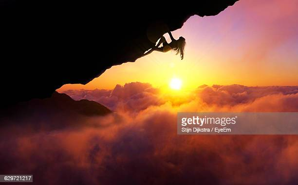 Woman Rock Climbing Over Cloudscape Against Sky During Sunset