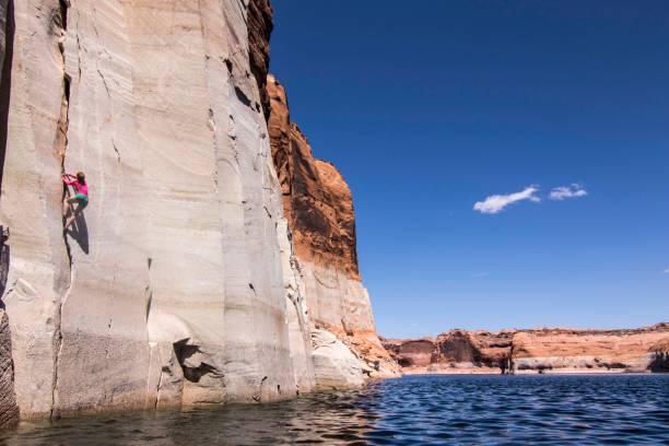 Woman rock climbing up cliff, Lake Powell, Utah, USA