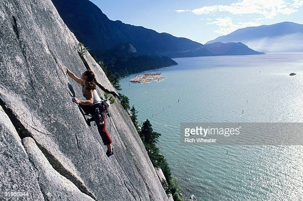 A woman rock climbing with water in the background in Squamish, British Columbia, Canada.