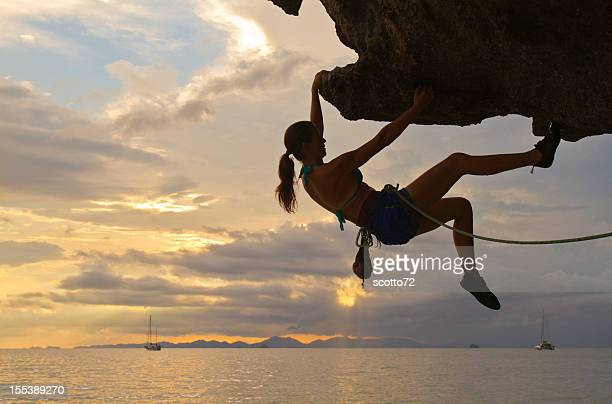 woman rockclimbing silhouette - rock overhang stock photos and pictures