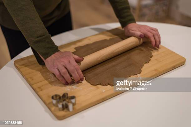 woman rolling out gingerbread dough on wooden board - rolling stock pictures, royalty-free photos & images