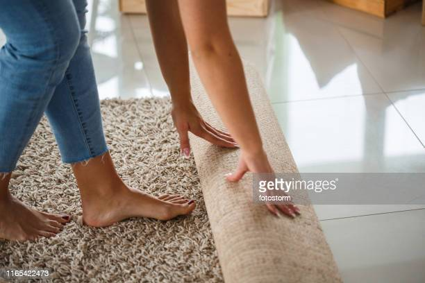 woman rolling out new rug - positioning stock pictures, royalty-free photos & images