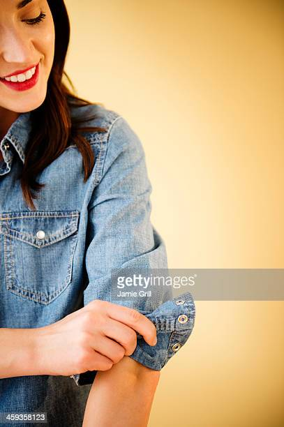woman rolling up her sleeves - long sleeved stock pictures, royalty-free photos & images