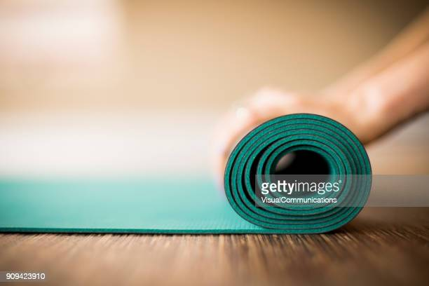 woman rolling up yoga mat. - pilates foto e immagini stock