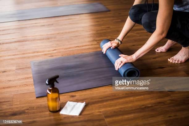 近くの消毒剤でヨガマットを巻き上げる女性。 - エクササイズマット ストックフォトと画像