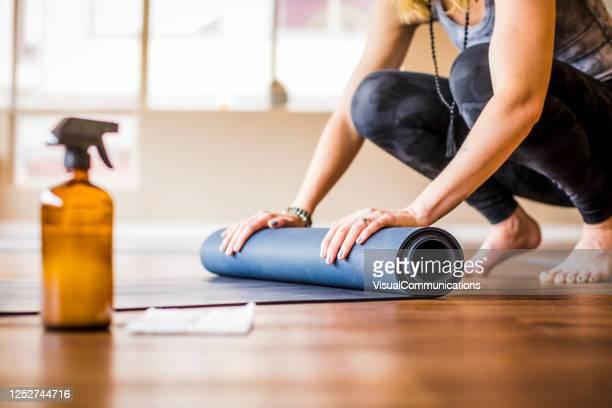 vrouw die yogamat met ontsmettingsmiddel dichtbij rolt. - fitnessmat stockfoto's en -beelden