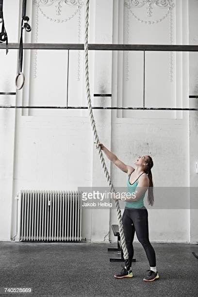 Woman rope climbing in cross training gym