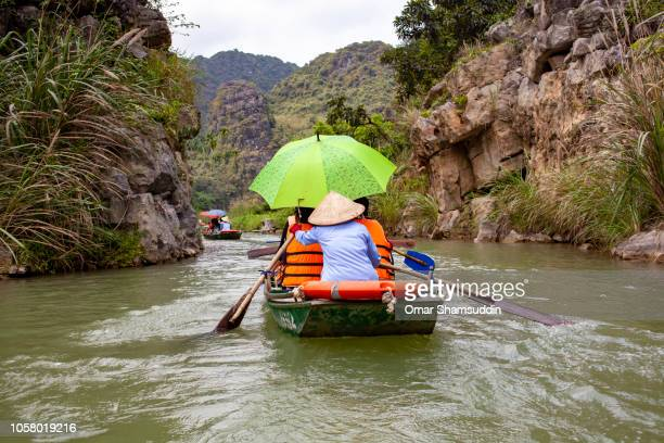 a woman rowing a boat at ecotourism trang an boat tour - omar shamsuddin stock pictures, royalty-free photos & images