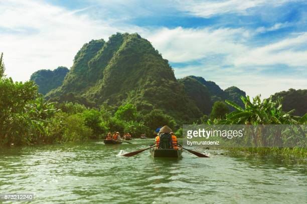 woman rowing boat in trang an, ninh binh, vietnam - grotto stock pictures, royalty-free photos & images