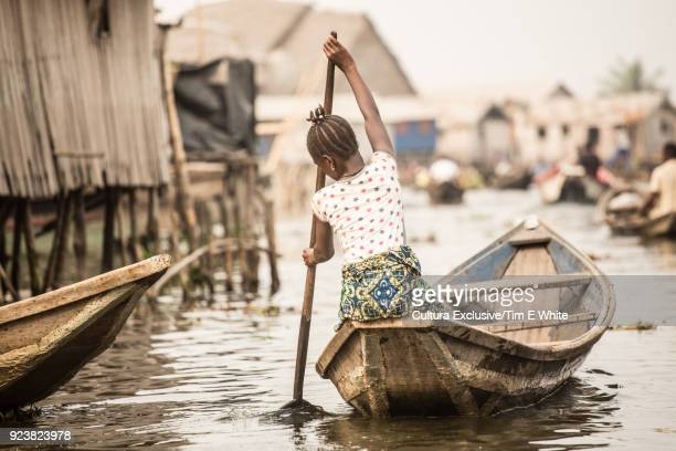 Woman rowing boat, rear view, Ganvie, Littoral, Benin, Africa