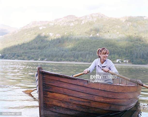 woman rowing boat, smiling - rowing boat stock pictures, royalty-free photos & images