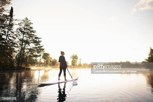 Woman rowing paddle board on still lake