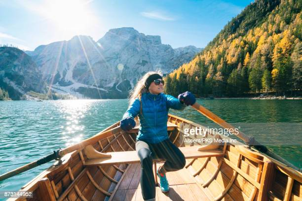 woman rowing wooden boat on alpine lake - pragser wildsee stock pictures, royalty-free photos & images