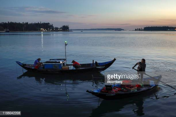 A woman rows a boat past fishermen sorting fish in Tan Quang harbor in Quang Nam province Vietnam on Wednesday June 26 2019 Fishermen are on the...