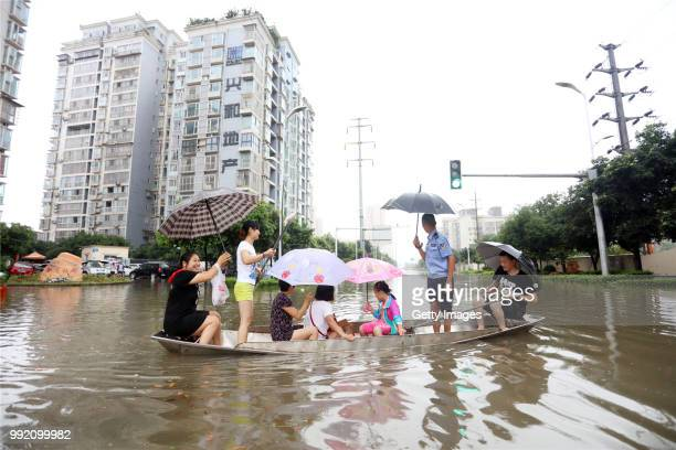 A woman rows a boat to transfer people in a flooded street on July 3 2018 in Suining Sichuan Province of China Heavy rains have hit more than eight...