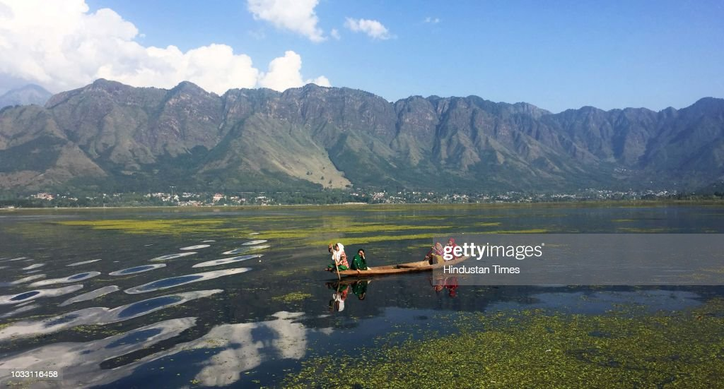 A woman rows her boat as her fellow passengers sit on a boat on sunny day in the waters of Dal Lake, on September 14, 2018 in Srinagar, India.
