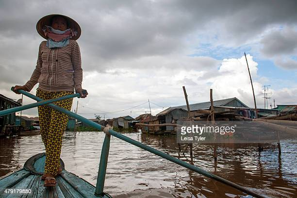 A woman rows past a floating village where fish are raised in suspended metal nets under people's houses at Chao Doc a town on the Bassac River in...