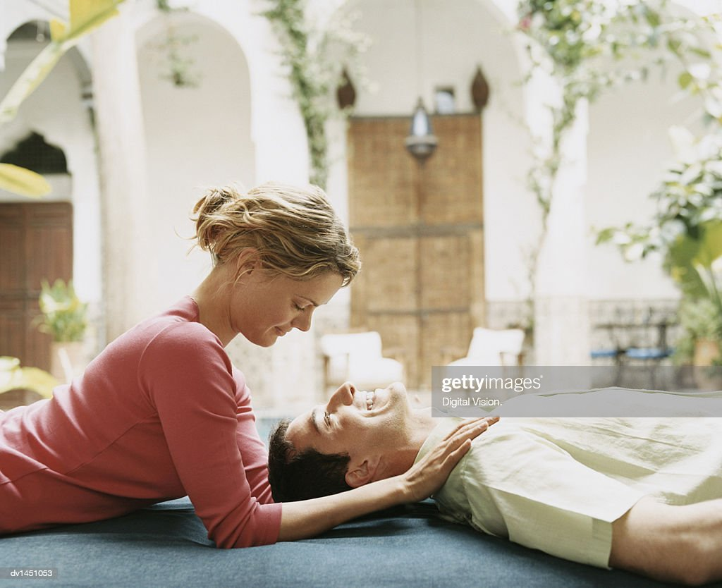 Woman Rubbing a Mans Shoulders as They Lie in an Outdoor Courtyard : ストックフォト