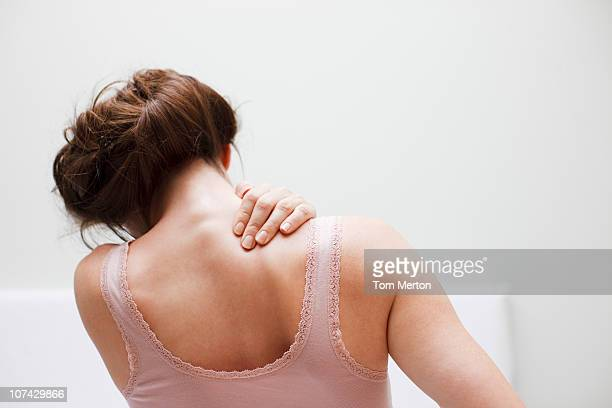 woman rubbing aching back - shoulder stock pictures, royalty-free photos & images