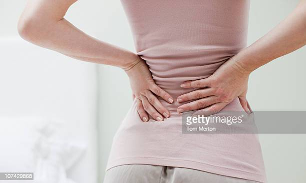 woman rubbing aching back - backache stock pictures, royalty-free photos & images