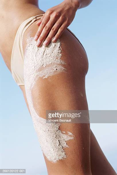 woman rubbing beauty scrub into leg, mid section - frau gespreizte beine stock-fotos und bilder