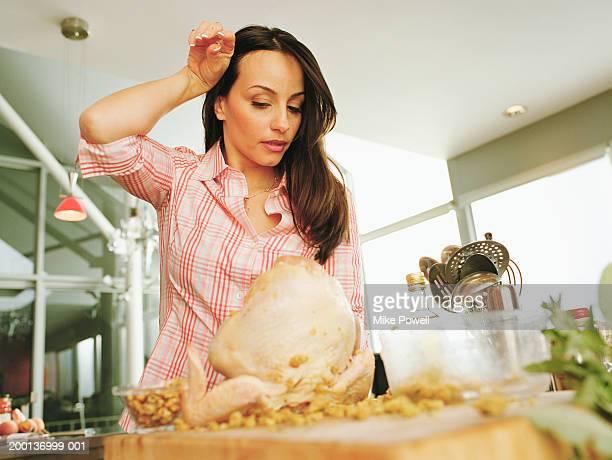 Woman rubbing dirty hand on head, stuffed raw turkey on cutting board