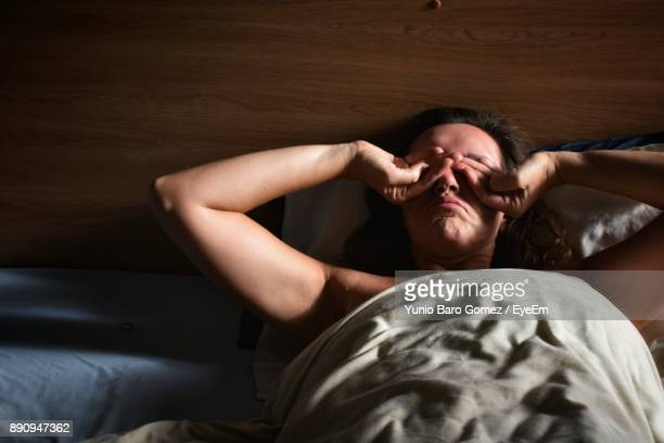 Woman Rubbing Eyes While Lying On Bed At Home