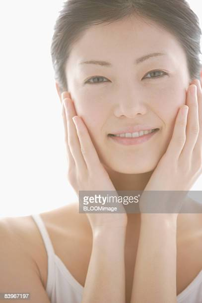 Woman rubbing face lotion into cheeks