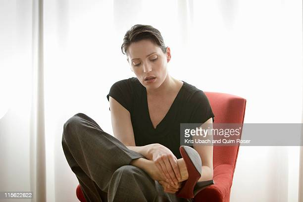 woman rubbing her feet - rubbing stock pictures, royalty-free photos & images