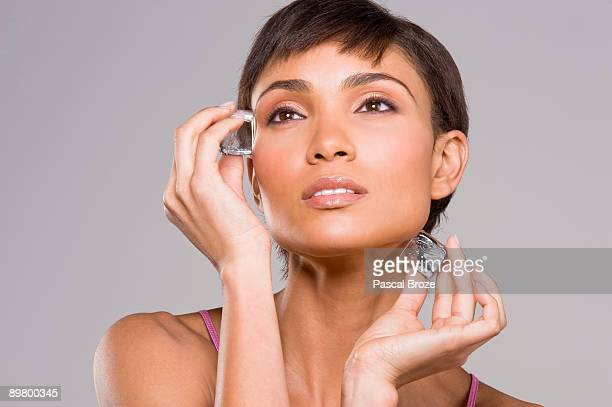 woman rubbing ice cubes on her face - rubbing stock pictures, royalty-free photos & images