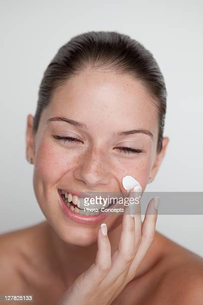 Frau reiben Creme auf Ihr Gesicht