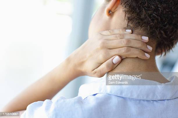 woman rubbing sore neck - backache stock pictures, royalty-free photos & images
