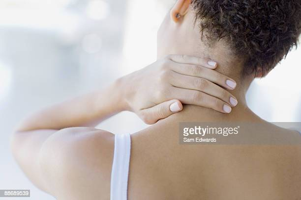 woman rubbing sore neck - back pain stock pictures, royalty-free photos & images