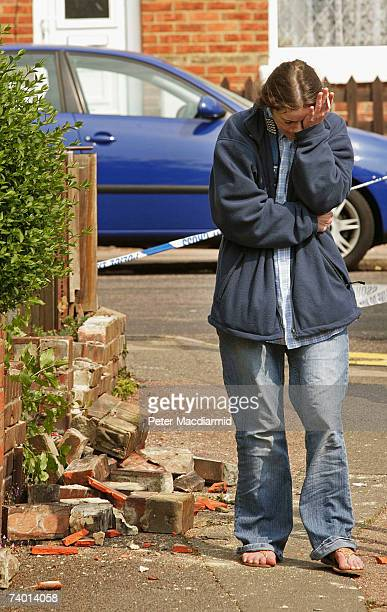 Woman rubs her eye as she stands near a damaged wall after an earthquake caused damage to houses on April 28, 2007 in Folkstone, Kent. The earth...