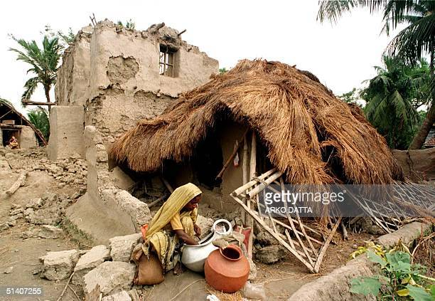 A woman rummages through her belongings as she tries to salvage whatever remains of her ruined thatched home 01 November 1999 in Barunda village in...