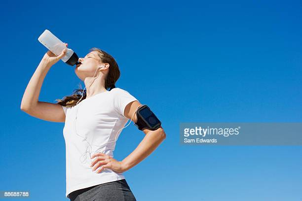 woman runner drinking from water bottle - thirsty stock pictures, royalty-free photos & images