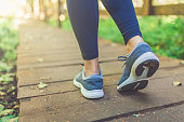 Woman runner feet walking in nature. Close up on shoes. Healthy lifestyle fitness concept.