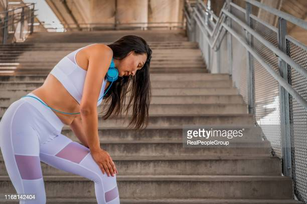 woman runner got sports injury - down on one knee stock pictures, royalty-free photos & images