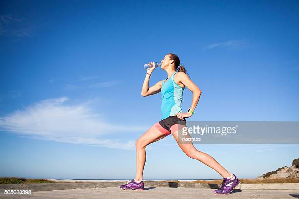 Woman runner stretching and drinking water