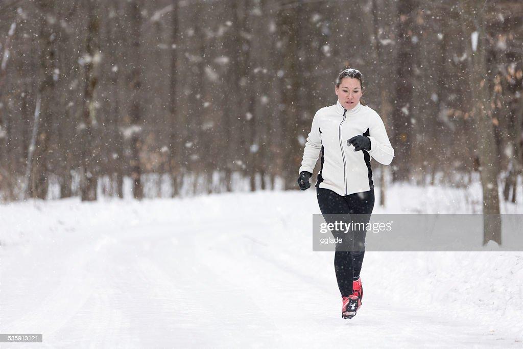 Mujer corredor capacitación en Snowstorm : Foto de stock